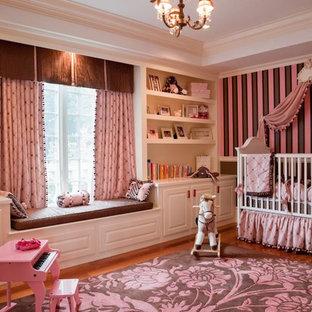 Immagine di un'ampia cameretta per neonata classica con pareti rosa e pavimento in legno massello medio