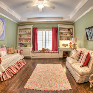 This is an example of a medium sized traditional nursery for girls in Atlanta with green walls and medium hardwood flooring.