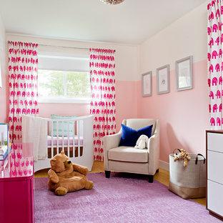 Cette image montre une chambre de bébé fille traditionnelle de taille moyenne avec un mur rose, un sol en bois clair et un sol violet.