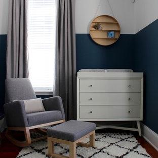 Mid-sized minimalist boy medium tone wood floor nursery photo in Philadelphia with blue walls