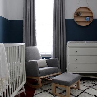 Imagen de habitación de bebé niño moderna, de tamaño medio, con paredes azules y suelo de madera en tonos medios