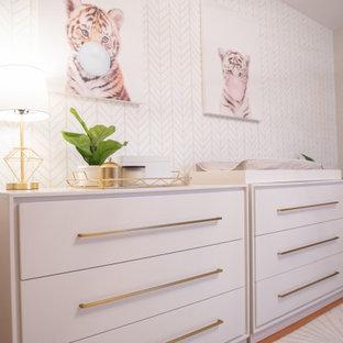 Cette image montre une chambre de bébé neutre minimaliste de taille moyenne avec un mur gris, sol en stratifié et un sol marron.