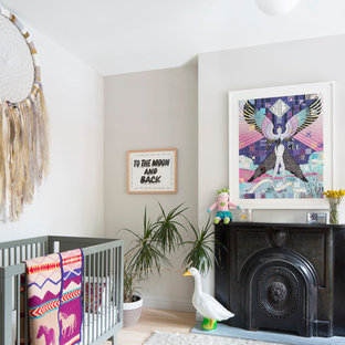 This is an example of a medium sized bohemian nursery for girls in New York with grey walls, light hardwood flooring and beige floors.