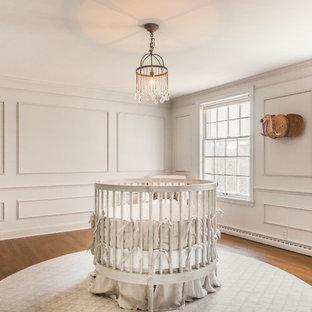 Modelo de habitación de bebé neutra tradicional renovada, de tamaño medio, con paredes beige y suelo de madera en tonos medios