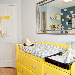 Imagen de habitación de bebé neutra clásica renovada con paredes grises y suelo de madera en tonos medios