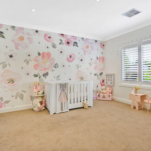 This is an example of a large traditional nursery for girls in Sydney with beige walls, carpet and beige floor.