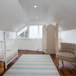 Foto de habitación de bebé niña de estilo americano, de tamaño medio, con paredes blancas, suelo de madera oscura y suelo marrón