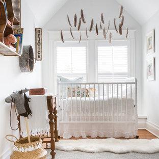Medium sized bohemian gender neutral nursery in Houston with white walls, medium hardwood flooring and brown floors.