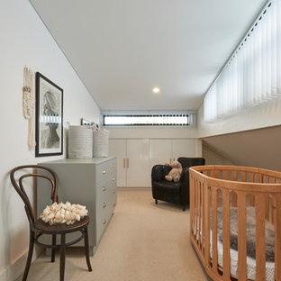 Imagen de habitación de bebé neutra contemporánea con paredes beige, suelo de cemento y suelo beige
