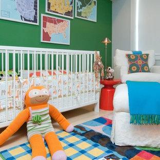 Immagine di una piccola cameretta per neonati neutra minimal con pareti verdi