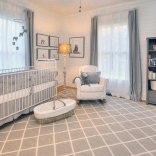Modelo de habitación de bebé neutra de estilo de casa de campo, de tamaño medio, con paredes blancas, suelo de madera en tonos medios y suelo gris