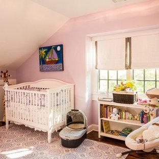 Diseño de habitación de bebé niña de estilo americano con paredes púrpuras y suelo de madera en tonos medios