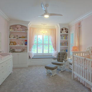Immagine di una cameretta per neonata tradizionale con pareti rosa e moquette