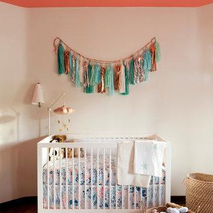 Diseño de habitación de bebé neutra clásica renovada con paredes beige y suelo de madera en tonos medios