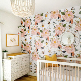 Medium sized eclectic nursery for girls in New York with multi-coloured walls, light hardwood flooring and brown floors.