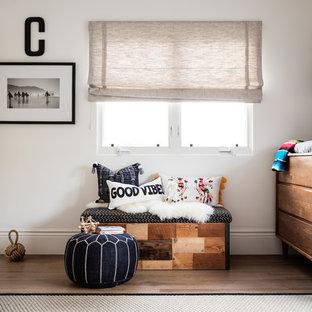 Cette image montre une chambre de bébé neutre marine avec un mur blanc et un sol en bois foncé.