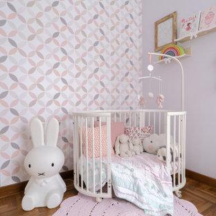 Aménagement d'une chambre de bébé contemporaine avec un mur violet, un sol en bois brun et un sol marron.