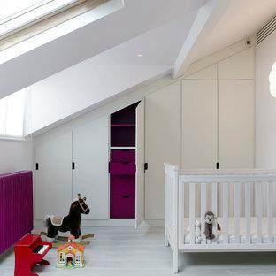 Idée de décoration pour une chambre de bébé neutre avec un mur blanc et un sol en bois peint.