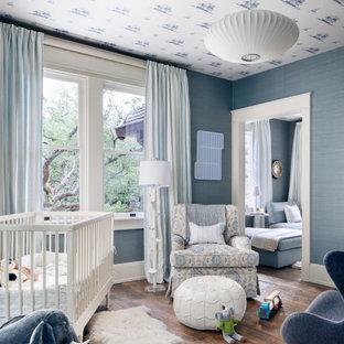 Foto di una cameretta per neonato minimal di medie dimensioni con pareti blu, pavimento in legno massello medio, pavimento marrone, soffitto in carta da parati e carta da parati