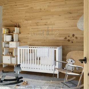 Inspiration for a scandinavian gender-neutral light wood floor nursery remodel in New York with beige walls