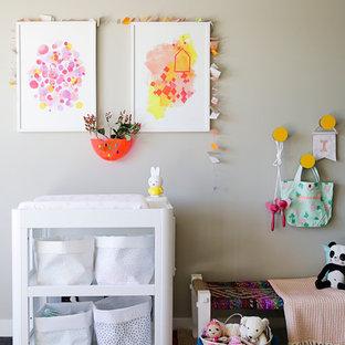 Idée de décoration pour une chambre de bébé neutre bohème avec un sol noir.