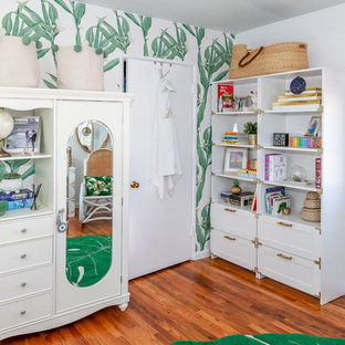 This is an example of a world-inspired gender neutral nursery in Los Angeles with white walls and medium hardwood flooring.