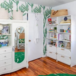 Island style gender-neutral medium tone wood floor nursery photo in Los Angeles with white walls