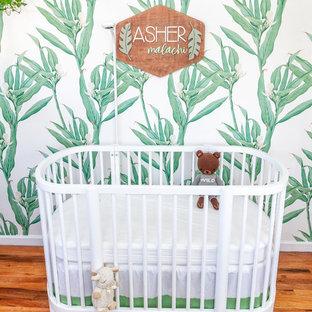 Modelo de habitación de bebé neutra exótica con paredes blancas y suelo de madera en tonos medios