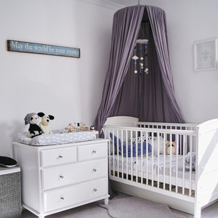 Inspiration for a traditional nursery for girls in London with white walls, carpet and grey floors.