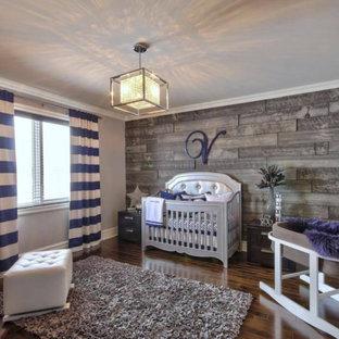 Diseño de habitación de bebé neutra rústica, grande, con paredes beige, suelo de madera oscura y suelo marrón