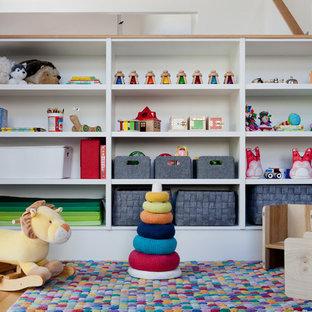 Gender-neutral medium tone wood floor nursery photo in Orange County with white walls