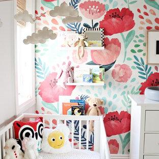 Ejemplo de habitación de bebé niña moderna, de tamaño medio, con paredes grises y suelo de madera clara