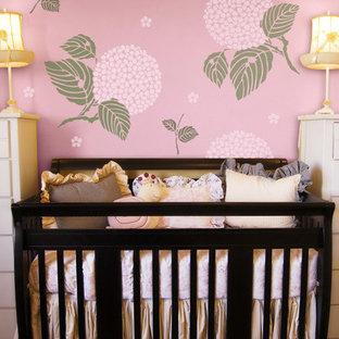 Foto di una cameretta per neonata etnica con pareti rosa