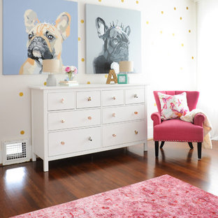 Inspiration pour une chambre de bébé traditionnelle de taille moyenne avec un mur blanc, un sol en bois foncé et un sol marron.