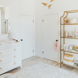 Small traditional nursery for girls in Los Angeles with light hardwood flooring, white walls and beige floors.