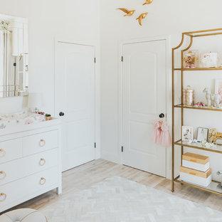 Modelo de habitación de bebé niña clásica renovada, pequeña, con suelo de madera clara, paredes blancas y suelo beige