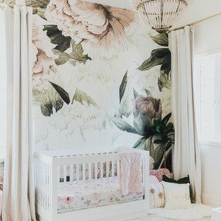 Modelo de habitación de bebé niña tradicional renovada, pequeña, con suelo de madera clara y paredes multicolor