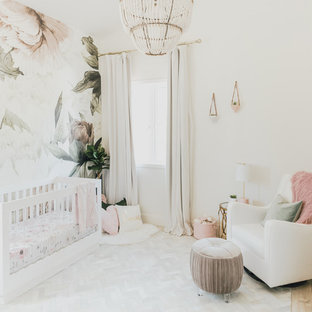 Small traditional nursery for girls in Los Angeles with multi-coloured walls and light hardwood flooring.