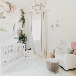 Modelo de habitación de bebé niña clásica renovada, pequeña, con paredes multicolor y suelo de madera clara