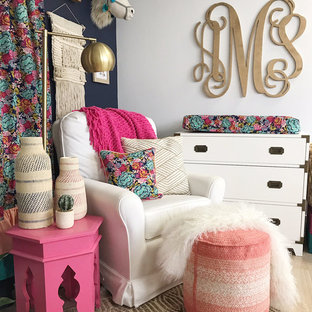 Design ideas for a small eclectic nursery for girls in Austin with blue walls, laminate floors and beige floors.