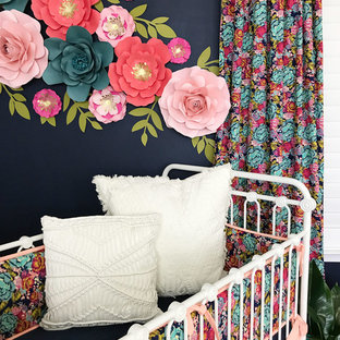 Small bohemian nursery for girls in Austin with blue walls, laminate floors and beige floors.