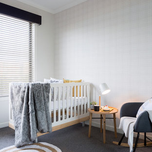 Transitional gender-neutral nursery in Melbourne with grey walls, carpet and grey floor.