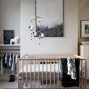 Photo of a small scandinavian gender neutral nursery in London with white walls, light hardwood flooring and beige floors.