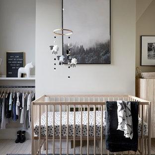 Esempio di una piccola cameretta per neonati neutra scandinava con pareti bianche, parquet chiaro e pavimento beige