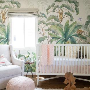 Design ideas for a medium sized bohemian nursery for girls in San Diego with medium hardwood flooring.