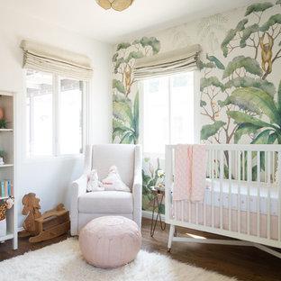 Inspiration pour une chambre de bébé fille design de taille moyenne avec un mur multicolore, un sol en bois foncé et un sol marron.