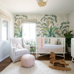 Design ideas for a medium sized eclectic nursery for girls in San Diego with medium hardwood flooring.