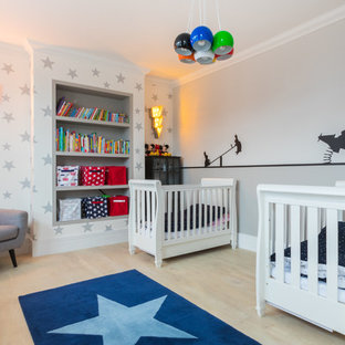 Photo of a classic gender neutral nursery in London with grey walls, light hardwood flooring and beige floors.