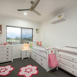 Inspiration for a contemporary nursery for girls in Other with white walls.