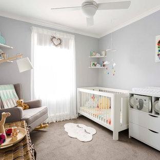 Diseño de habitación de bebé neutra actual con paredes grises, moqueta y suelo gris